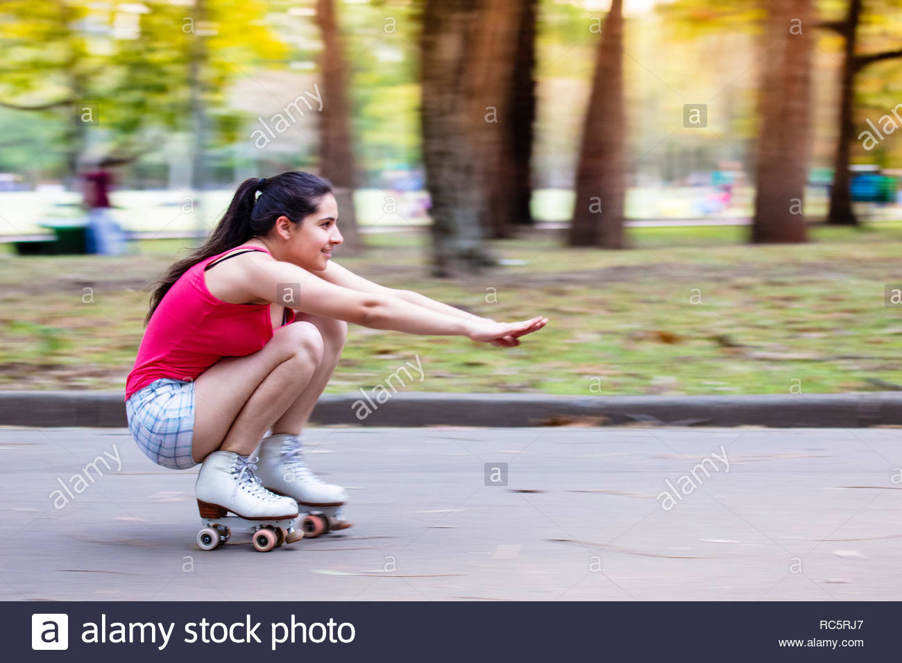Brazil, Sao Paulo, Ibirapuera Park. A teenaged Brazilian girl in shorts and a pink sleeveless top roller skating in Ibirapuera Park - Stock Image