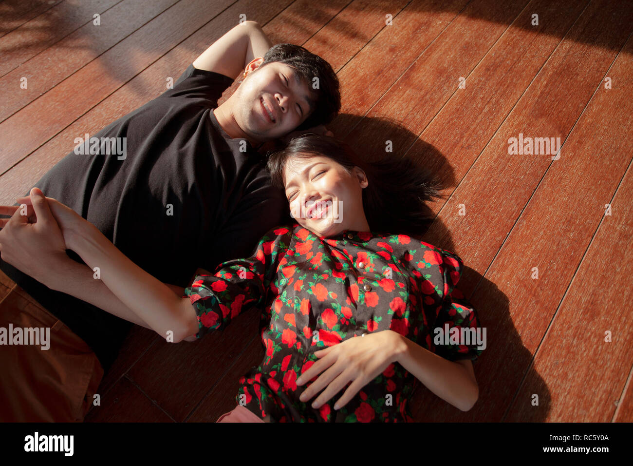asian younger man and woman lying on wood floor with happiness face - Stock Image