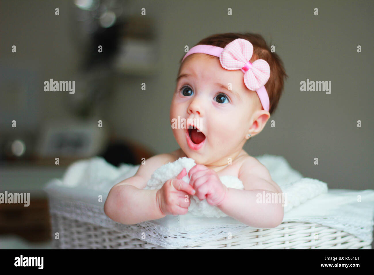 Cute Baby Girl With A Bow On Her Hair With Amazement Face