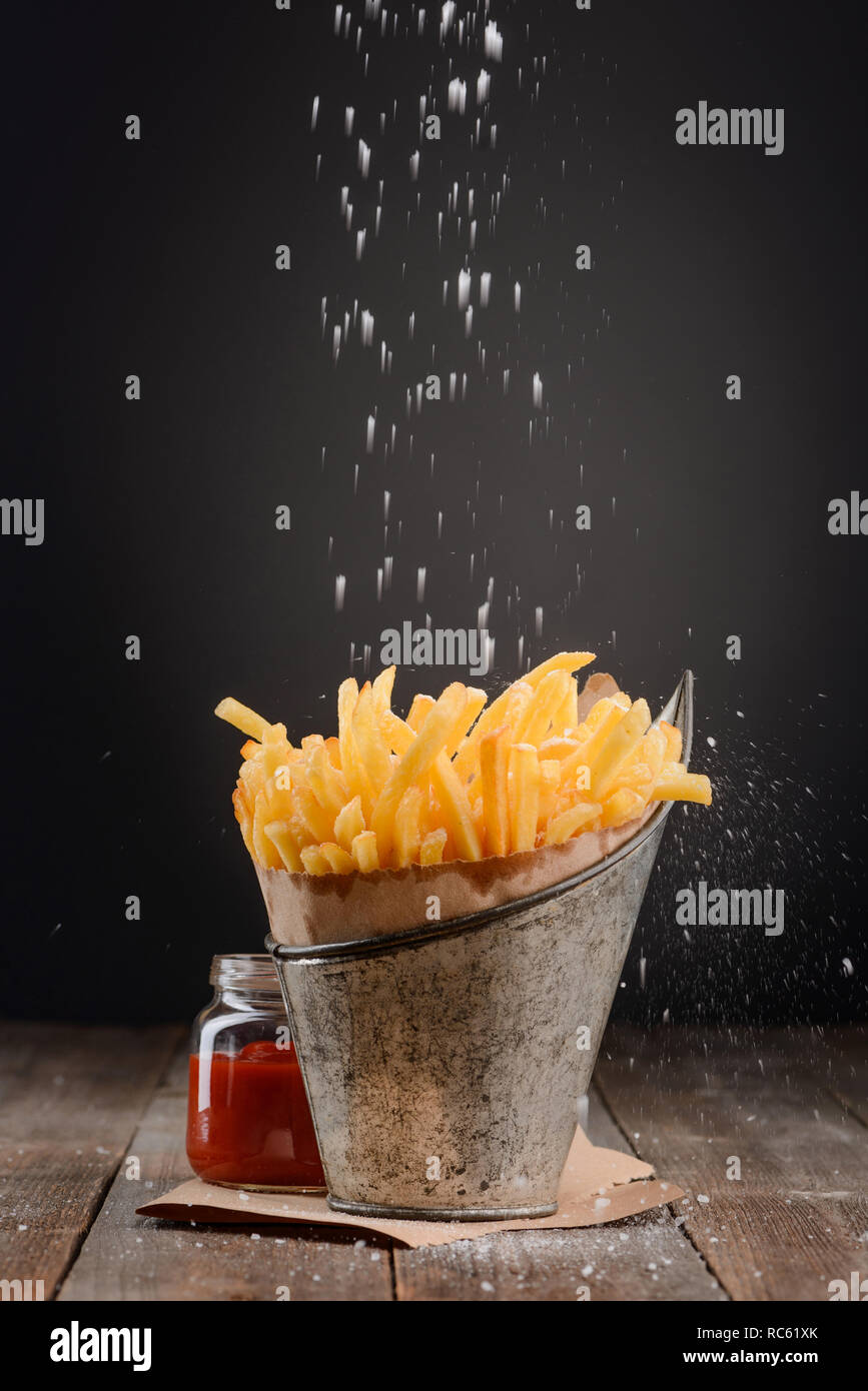 Adding salt to French fries - Stock Image