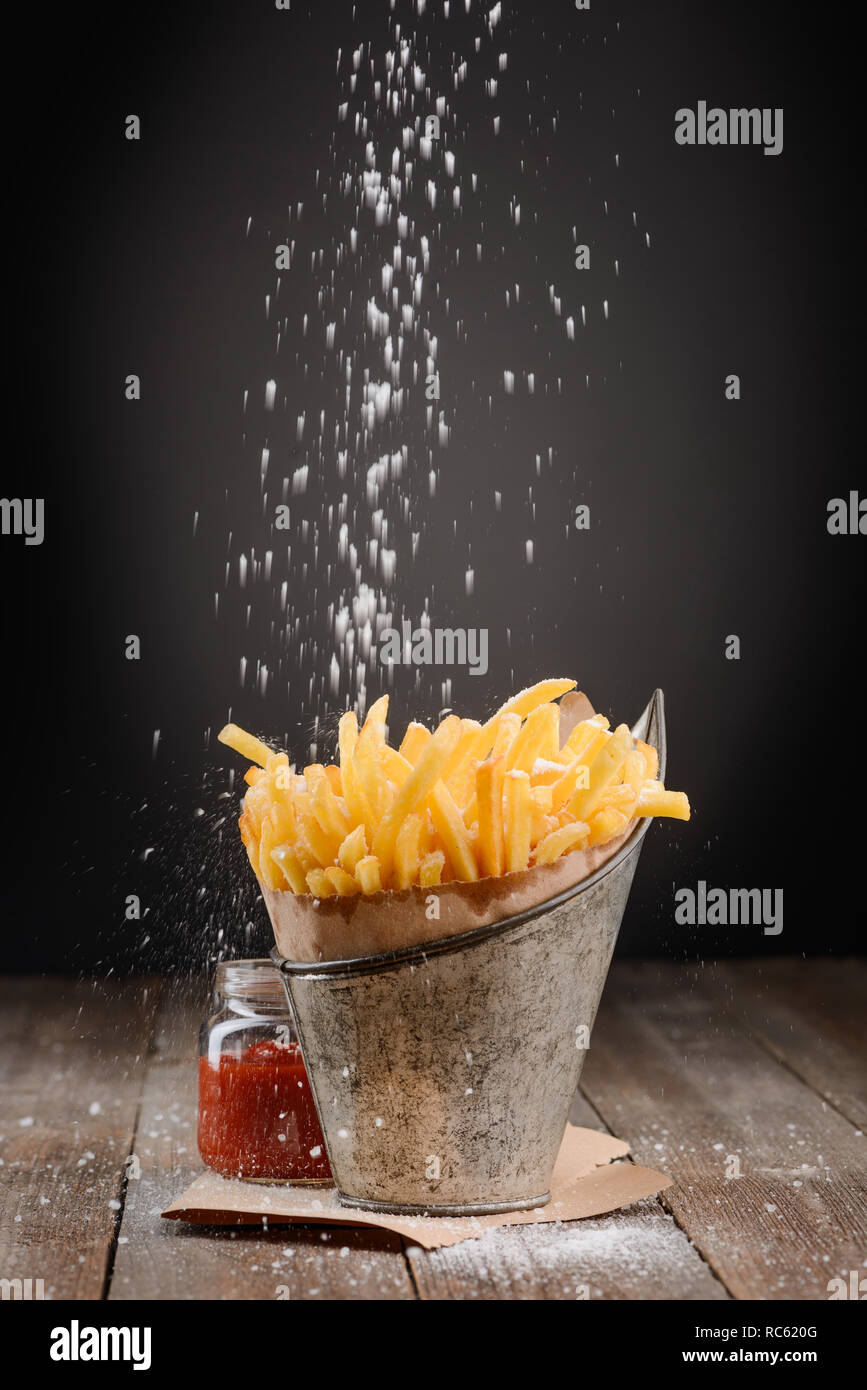 Salt sprinkling on French fries - Stock Image