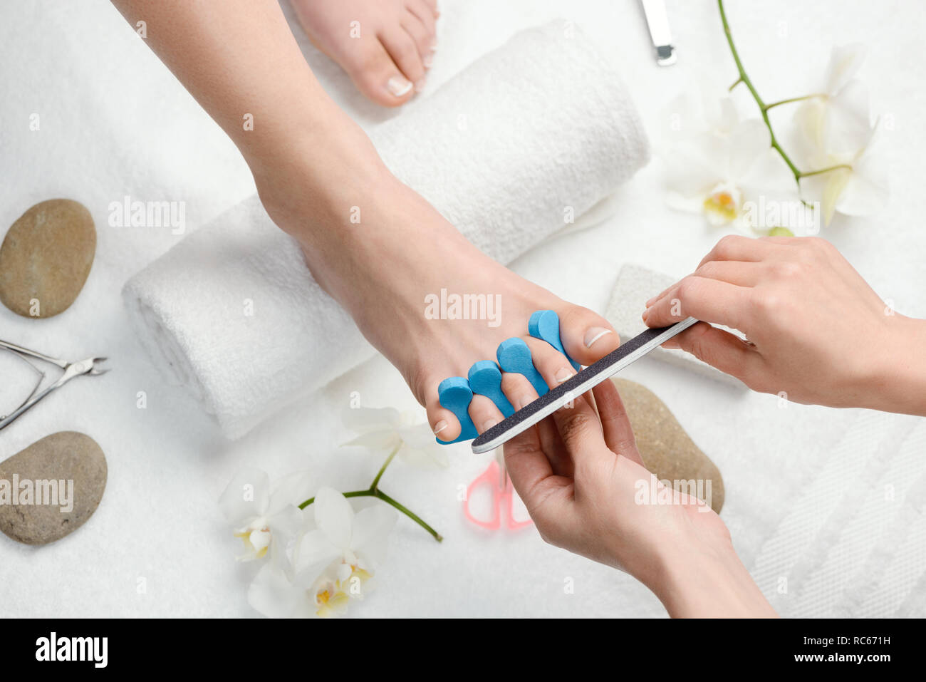 Pedicurist shaping toe nails - Stock Image