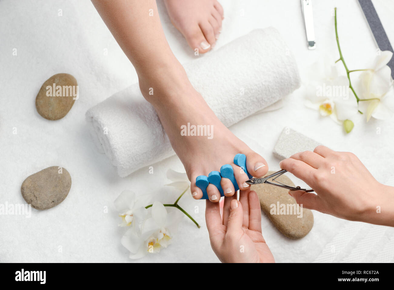 Pedicurist cutting cuticle with nippers - Stock Image