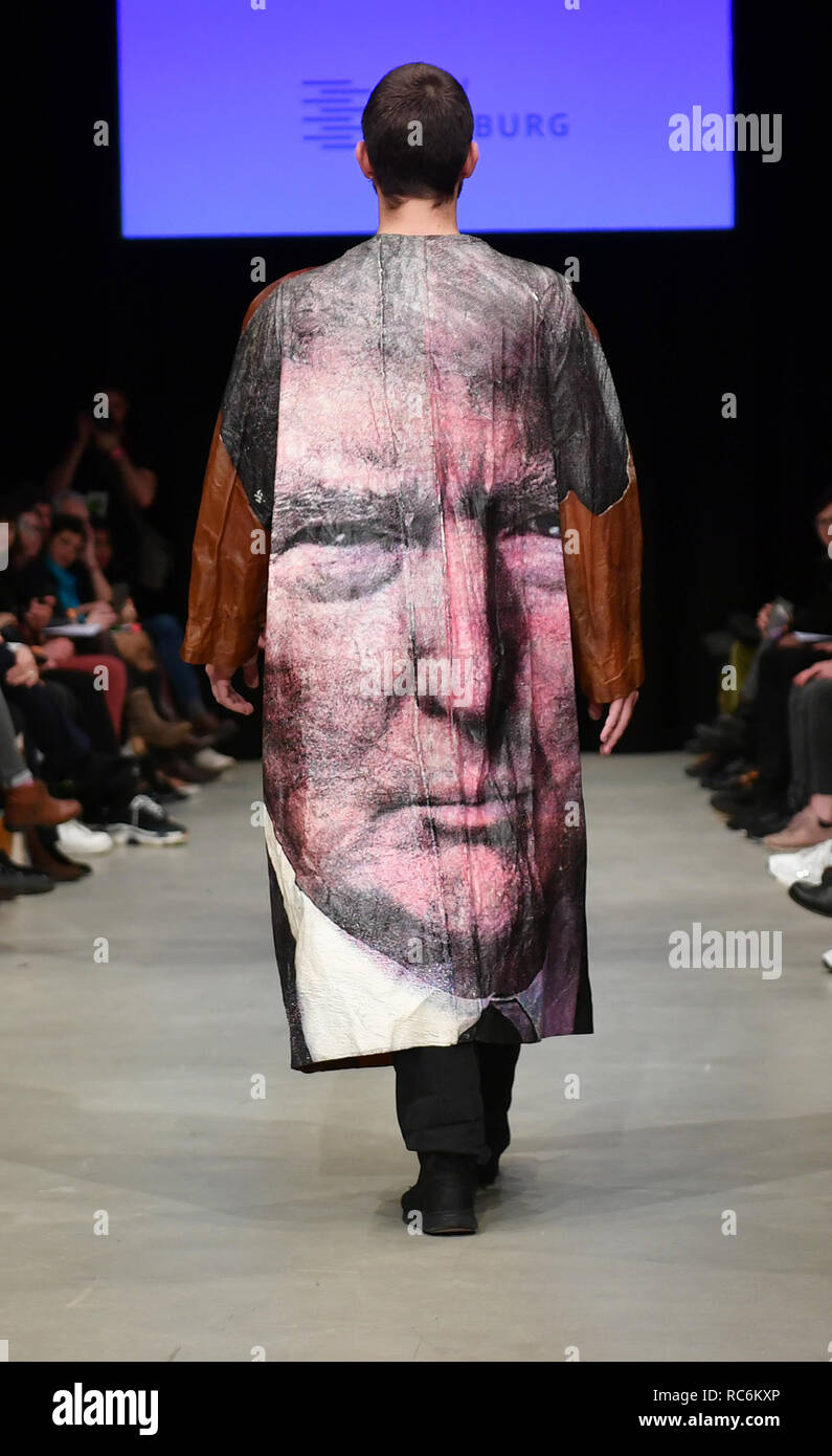 Berlin, Germany. 14th Jan, 2019. A model runs at the fashion show 'Neo.Fashion' with a coat with a trump motif designed by the young designer Bea Brücker. Young designers from various universities present their works at the Alexanderplatz transformer station. The collections for Spring/Summer 2019 will be presented at Berlin Fashion Week. Credit: Jens Kalaene/dpa/Alamy Live News - Stock Image