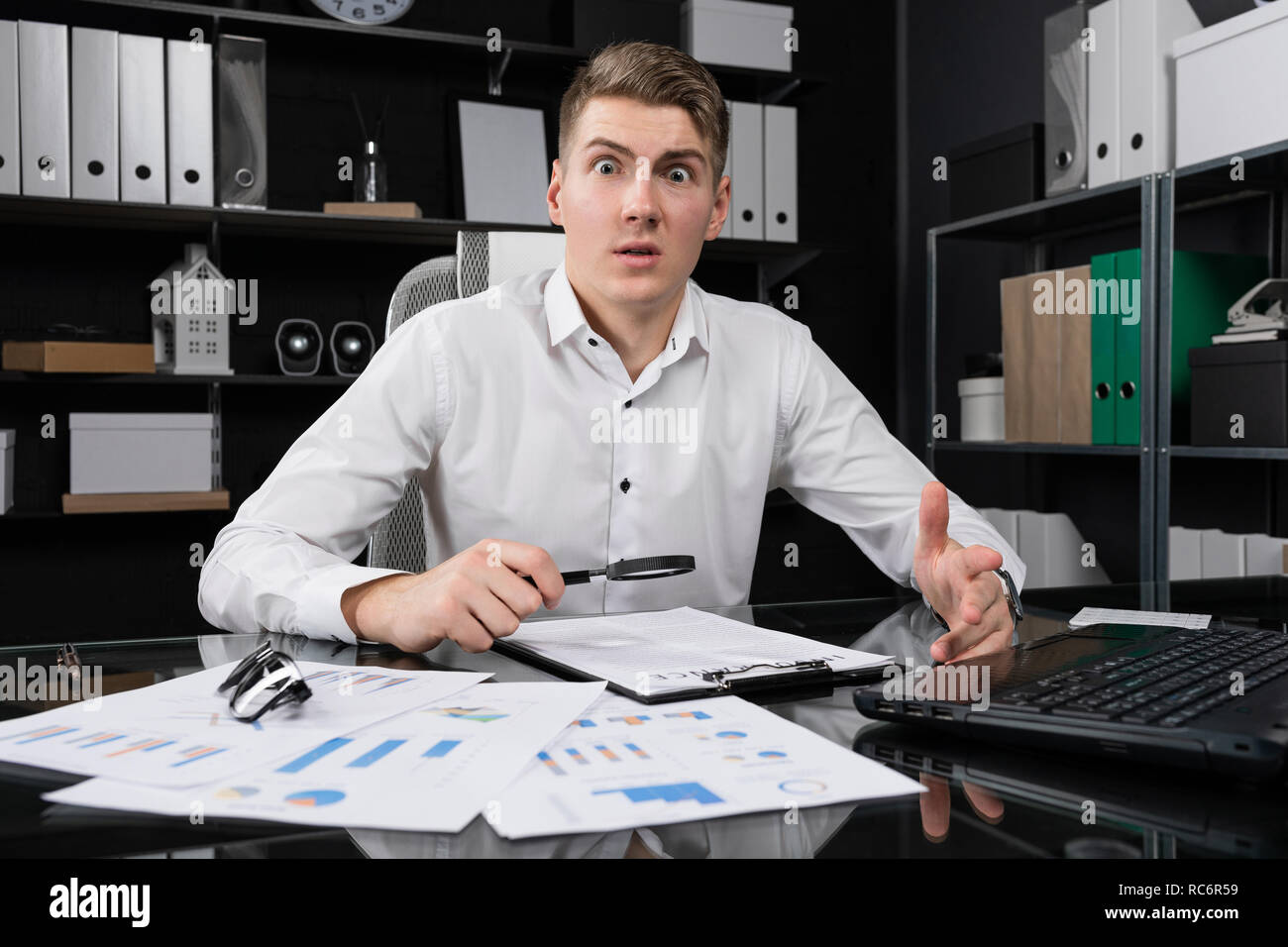 young man with magnifying glass and insurance is sitting at table in bright office - Stock Image