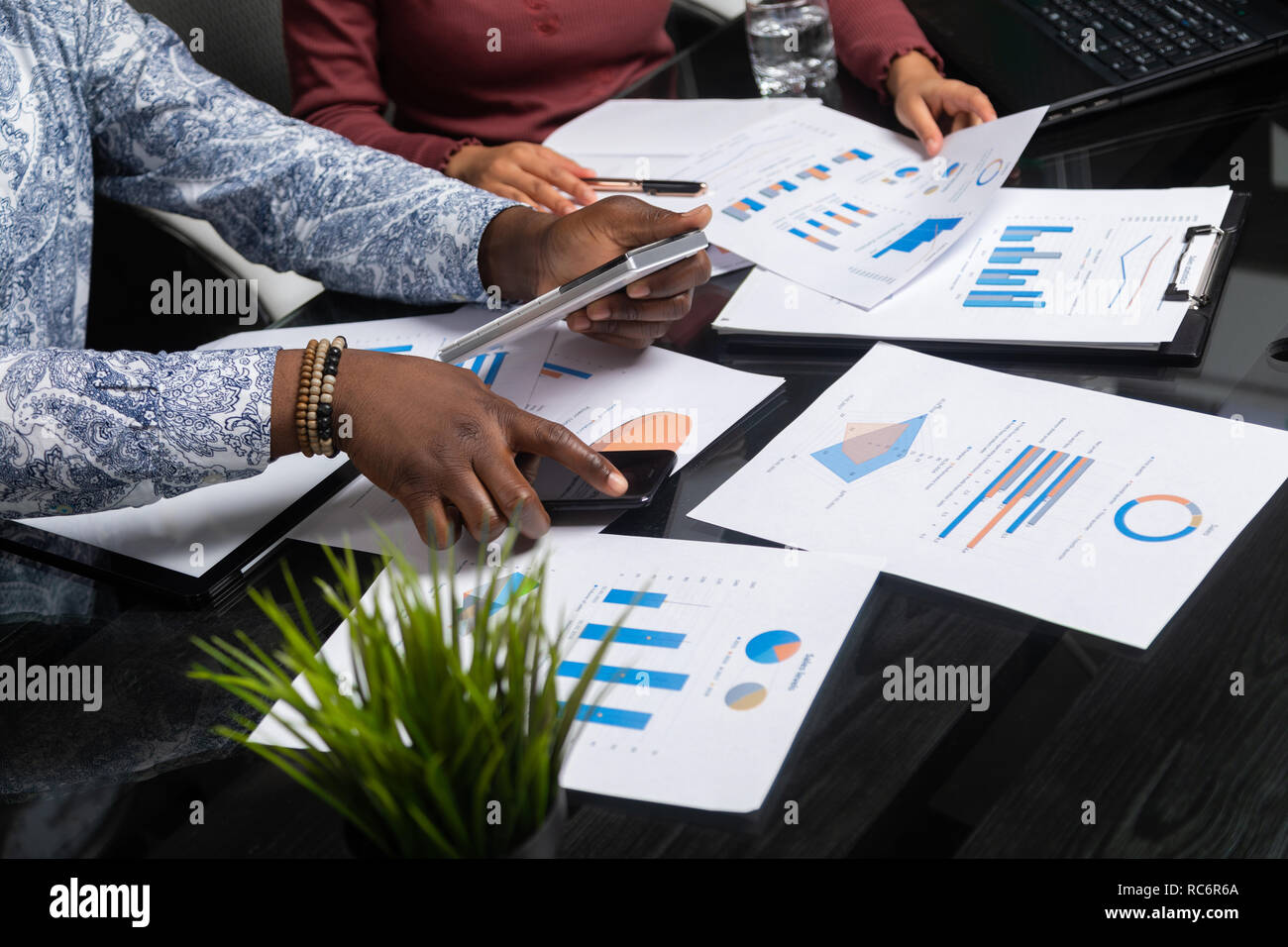 hands of dark-skinned people hold calculator against background of financial documents in business space closeup - Stock Image