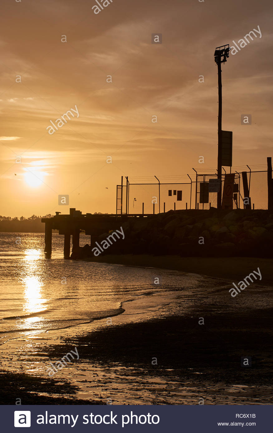 The infrastructure of Goodwood Island Wharf in silhouette, with a golden sky, and reflection off Clarence River's surface; as the sun sets in summer. - Stock Image