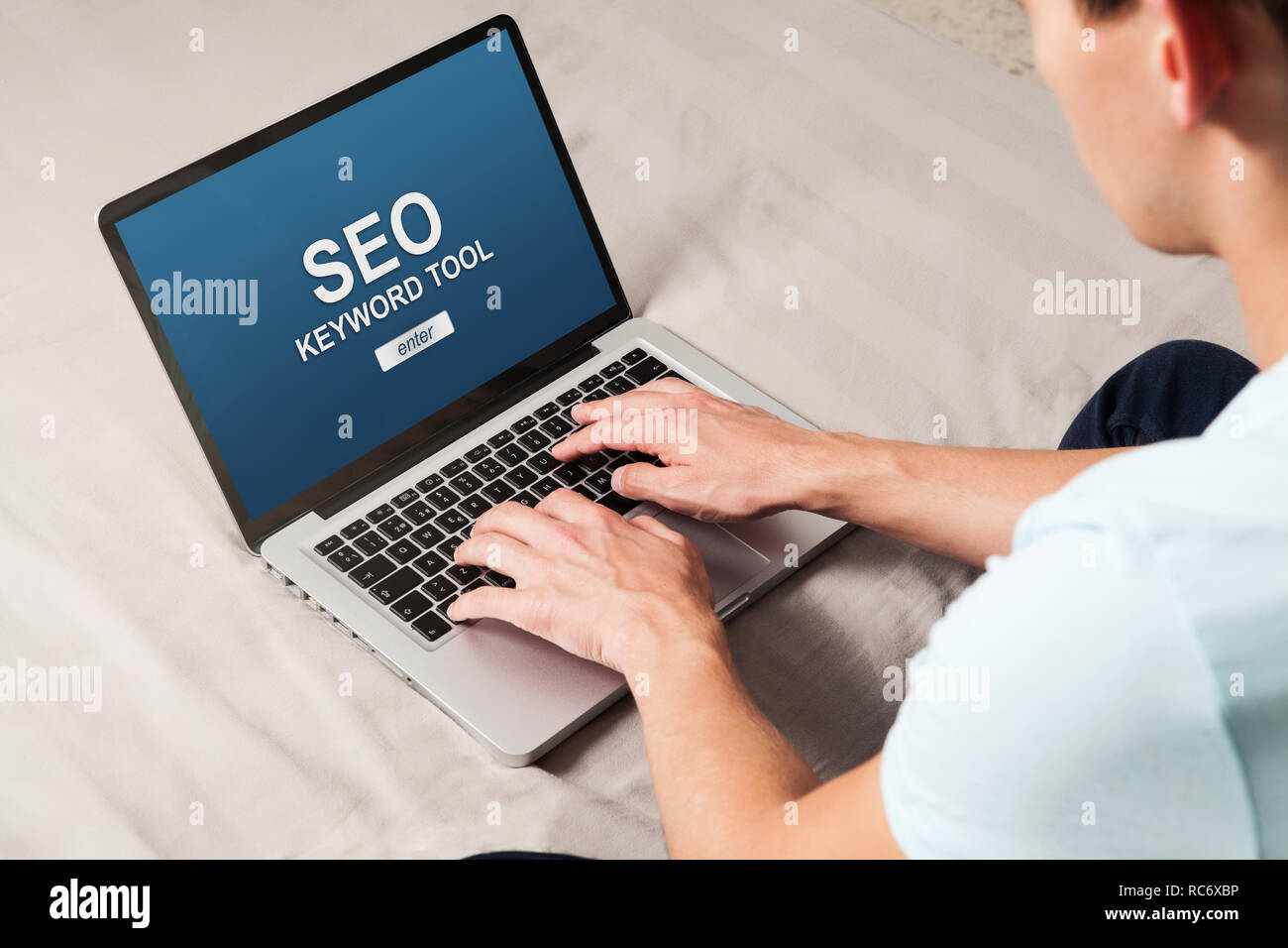 Man doing a SEO positioning in a website with a laptop computer. - Stock Image