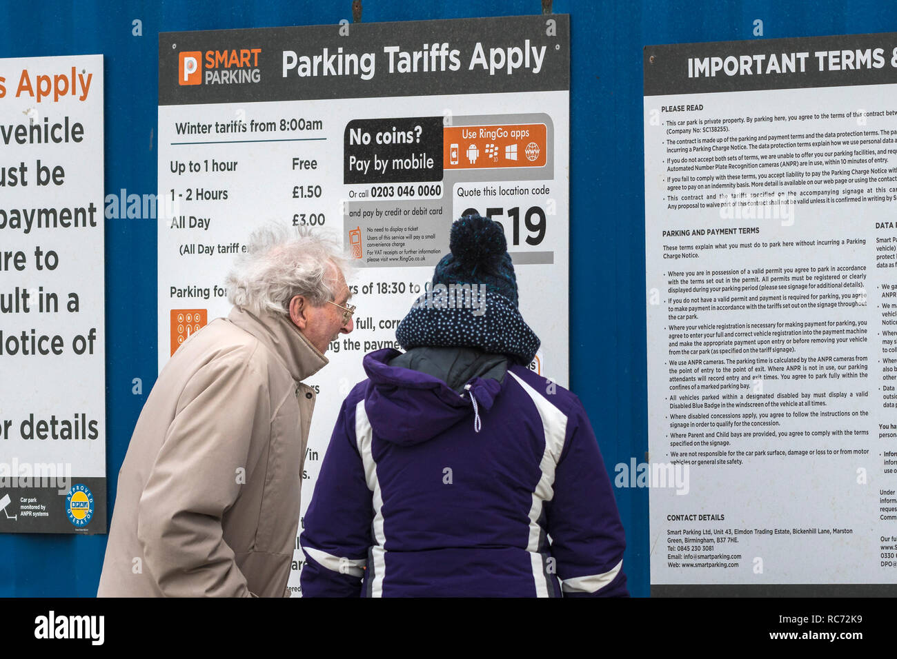 A mature couple looking at car parking rules on signs in Fistral Beach car park in Newquay Cornwall. - Stock Image
