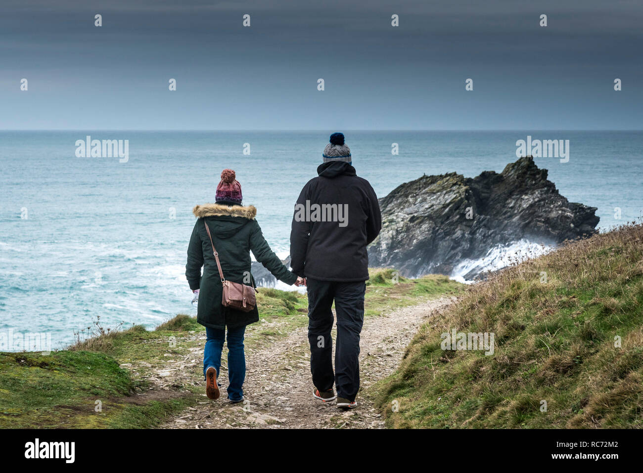 Two people walking on a coastal footpath holding hands and dressed for the cold chilly weather. - Stock Image