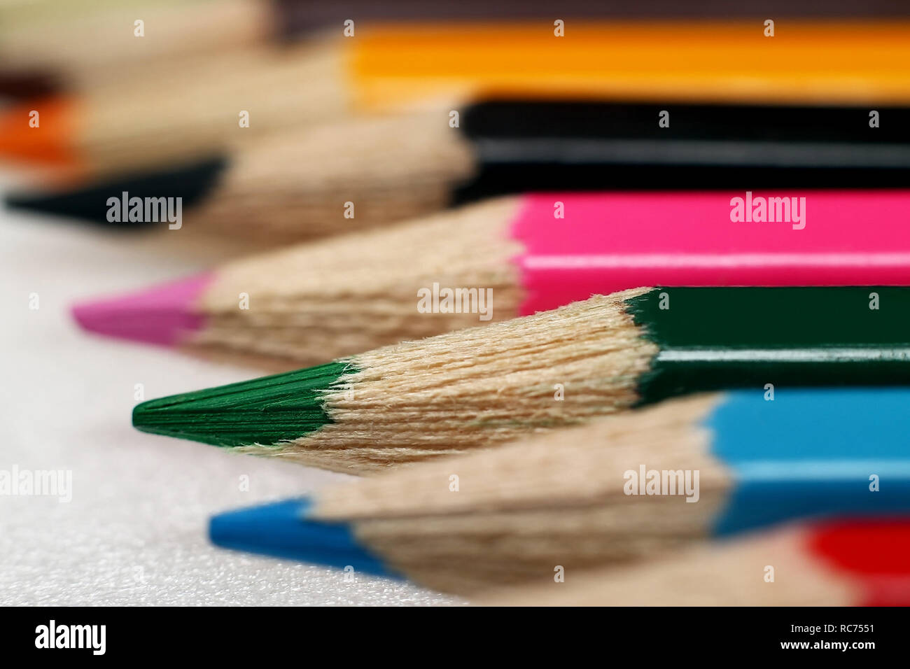 Colored pencils arranged in a row - Stock Image