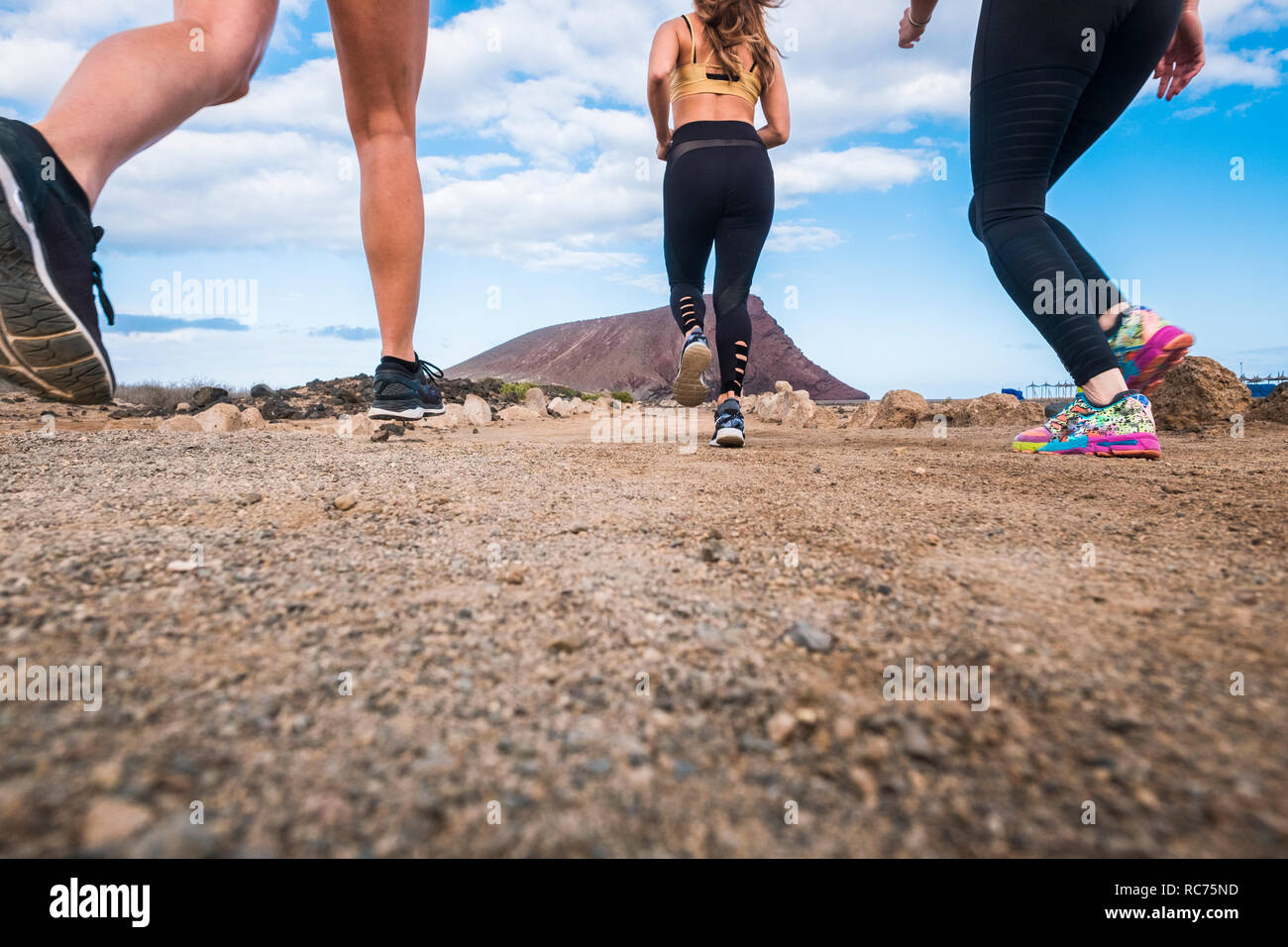 Ground point of view for three girls runner for jogging exercise running outdoor in the nature - fitness healthy lifestyle for young people enjoying t - Stock Image