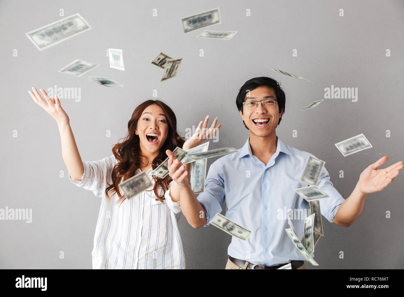 Happy asian business couple standing under money banknotes shower isolated over gray background - Stock Image