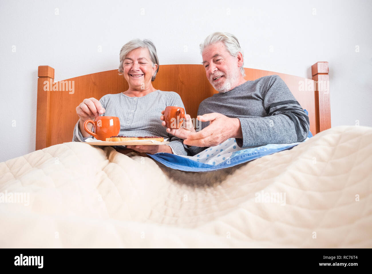 couple of adult senior at home doing breakfast together in the bed at morning - indoor activity for married people - ground view and man and woman hav Stock Photo