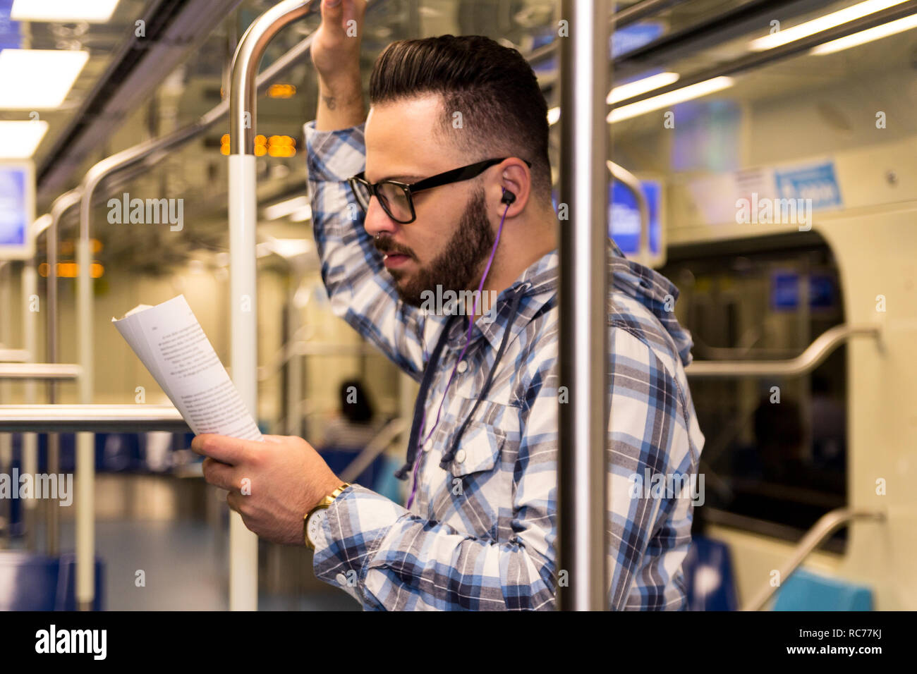 Concept of determination, commitment, concentration, journey. Smart scholar wearing checked pattern shirt and glasses in public transport. - Stock Image