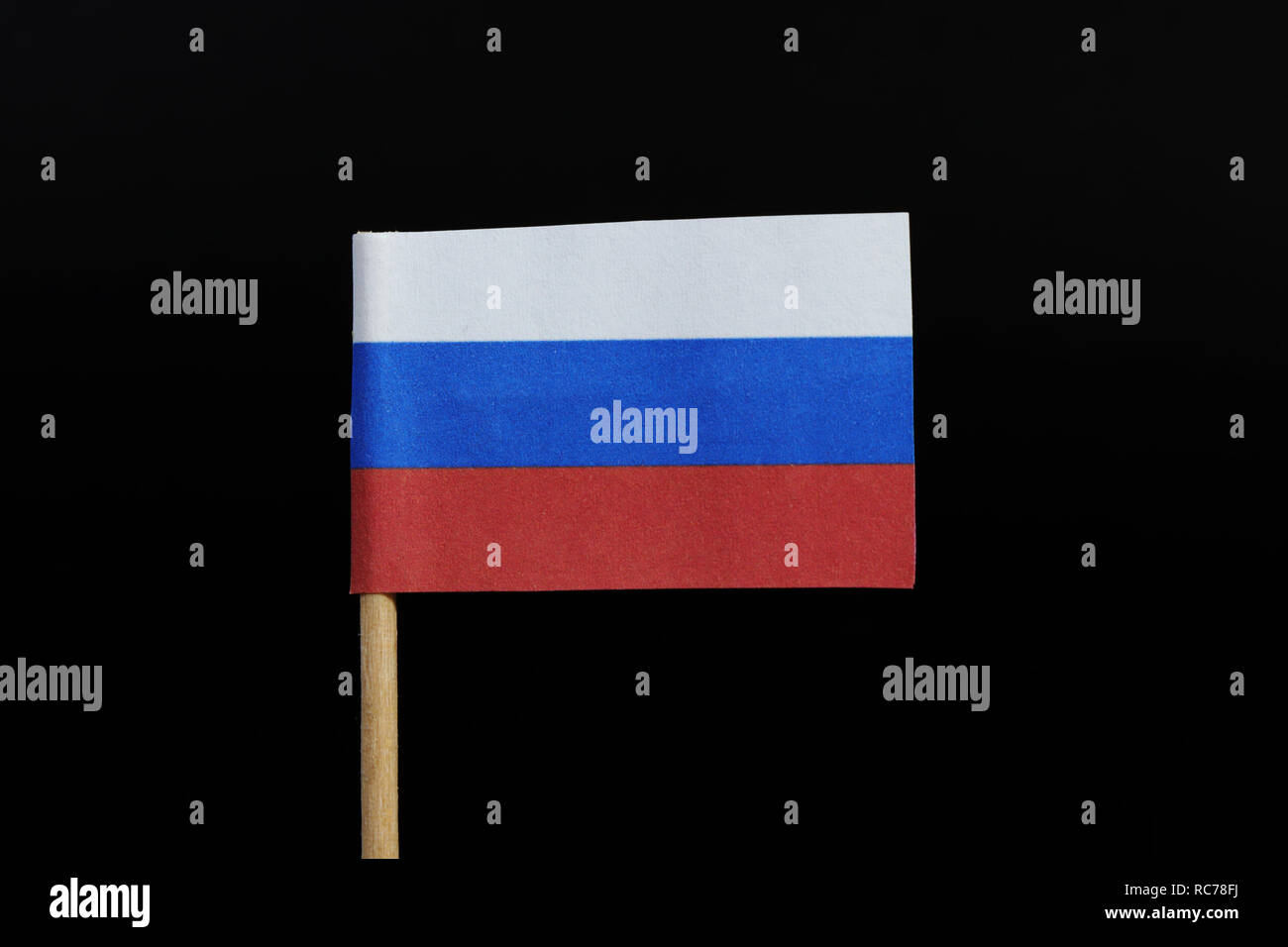 A original and national flag of Russia  on toothpick on black background. A horizontal tricolour of white, dark blue and red. - Stock Image