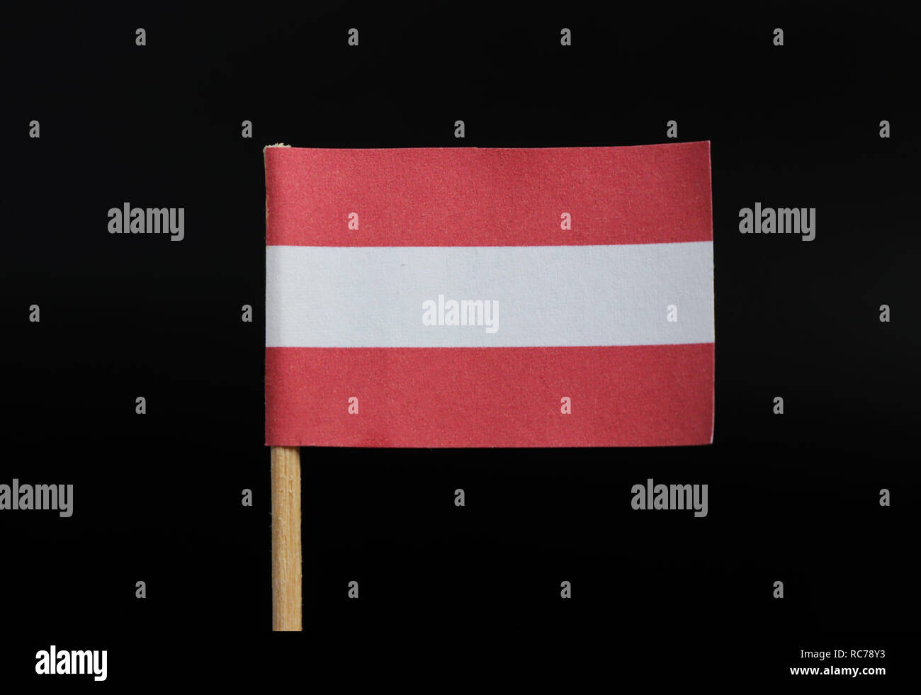 A unique and very simple flag of Austria on toothpick on black background. A horizontal triband of red (top and bottom) and white. - Stock Image