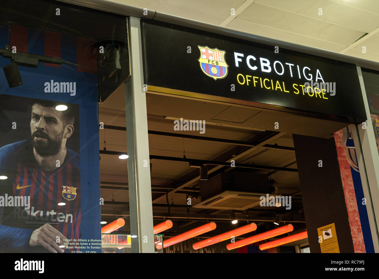 entrance to the fc botiga store of the fc barcelona footbal team with a poster by Gerard Pique in the shop window. Logo fc barcelona, Spain - Stock Image