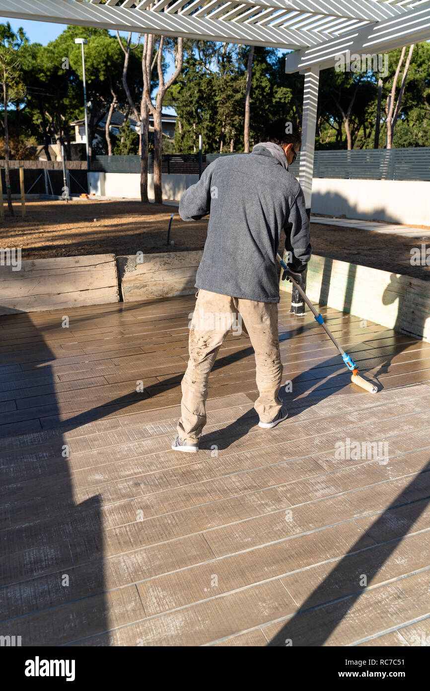 Construction worker painting the floor with epoxy based paint, hard durability , Barcelona, Spain - Stock Image