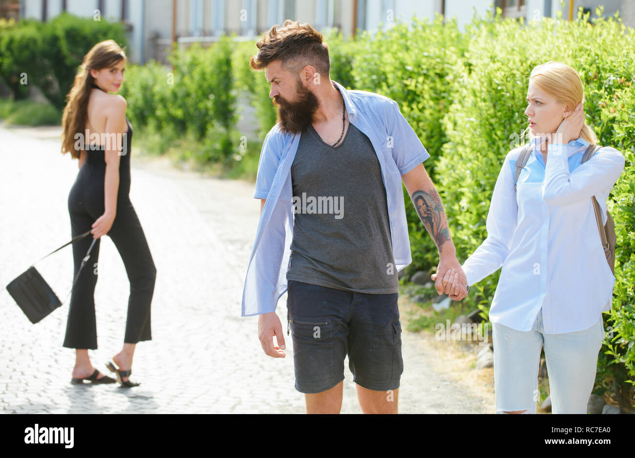 Are you with me. Hipster choosing between two women. Love triangle and threesome. Man cheating his wife or girlfriend. Bearded man looking at other girl. Betrayal and infidelity. Unfaithful love - Stock Image
