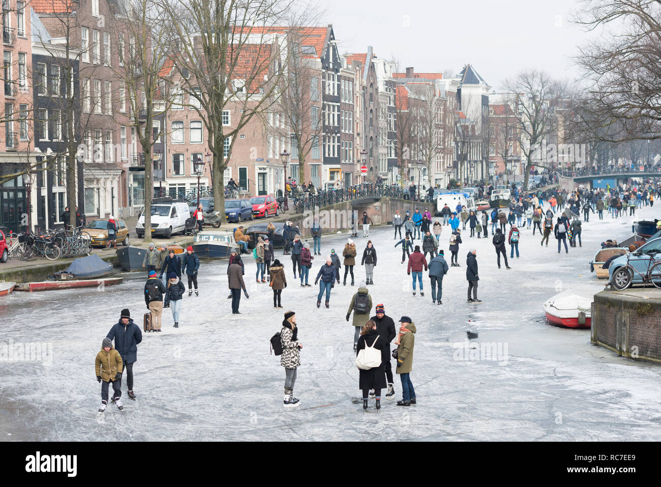 Ice skating people on frozen canal Prinsengracht, Amsterdam, The Netherlands. Stock Photo