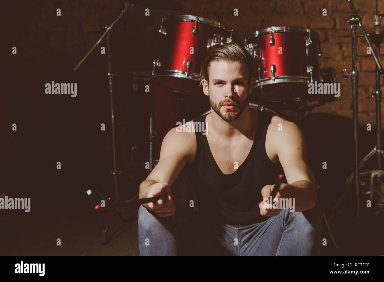 Got sticks. Man drummer with drumsticks instrument. Handsome man sit on stage at percussion instrument. Rock star or rocker. Enjoying instrumental music. Rock concert or rehearsal in music club - Stock Image