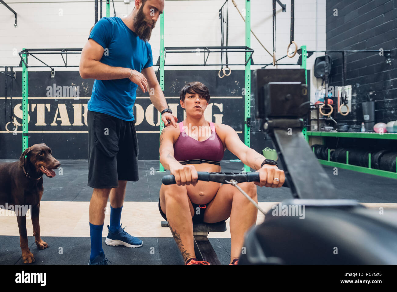 Trainer guiding pregnant woman on rowing machine in gym Stock Photo