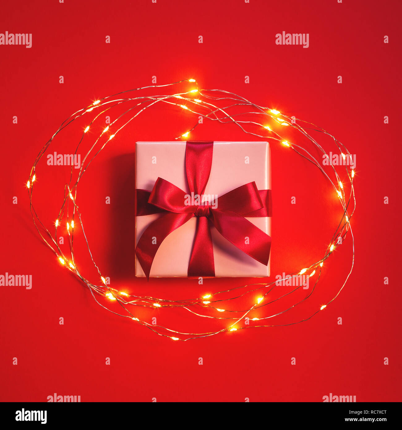 Gift box tied with red bow on red background with frame of garland lights. Top view. Stock Photo