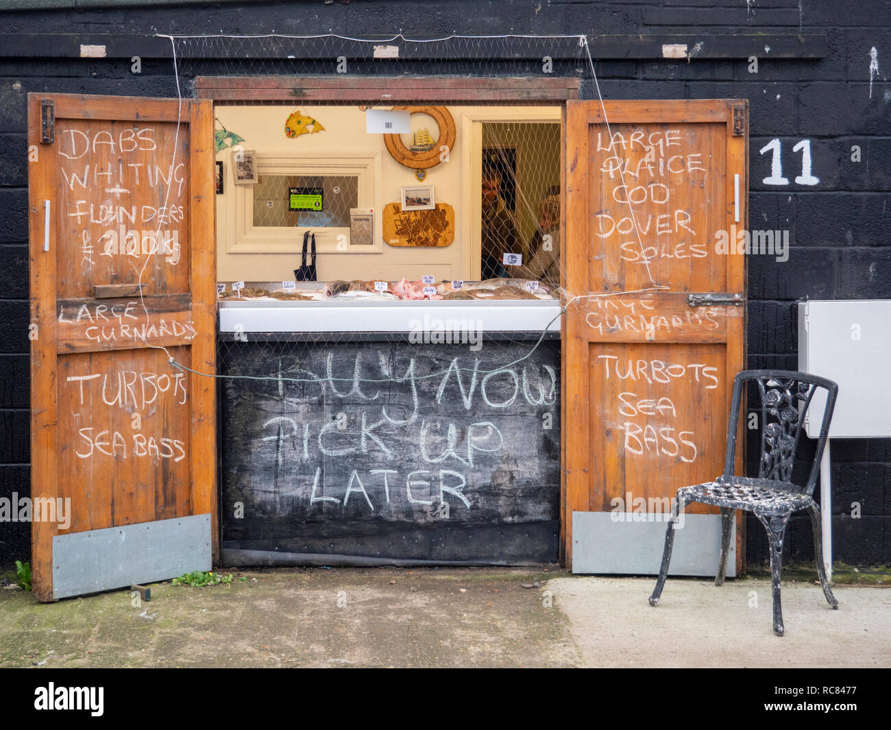 A fresh fish shop or shed in Hastings East Sussex UK with signs for fish on sale written in chalk on the walls. - Stock Image