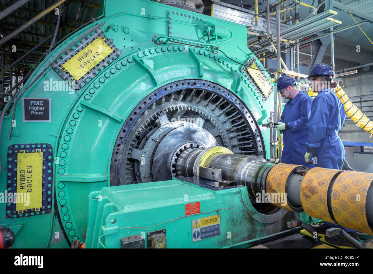 Engineers inspecting generator in nuclear power station during outage - Stock Image