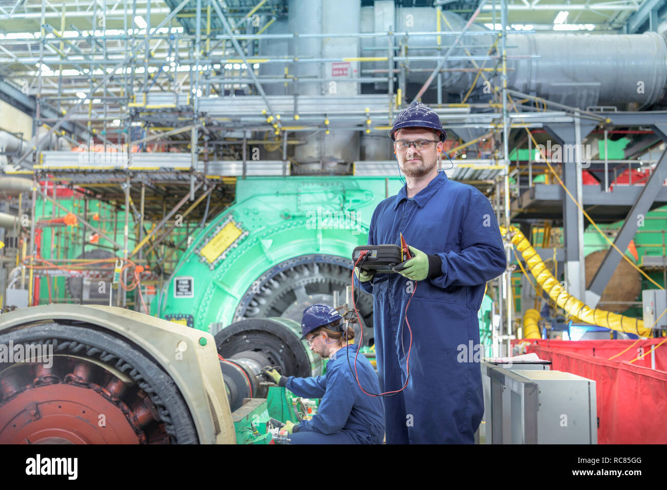 Portrait of engineer in turbine hall of nuclear power station during outage - Stock Image