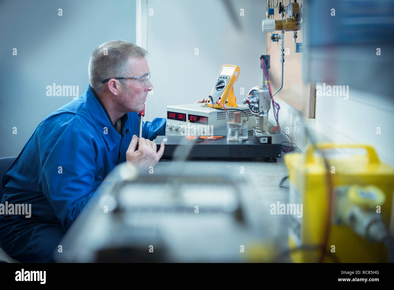 Engineer pressure testing sensors in nuclear power station during outage - Stock Image