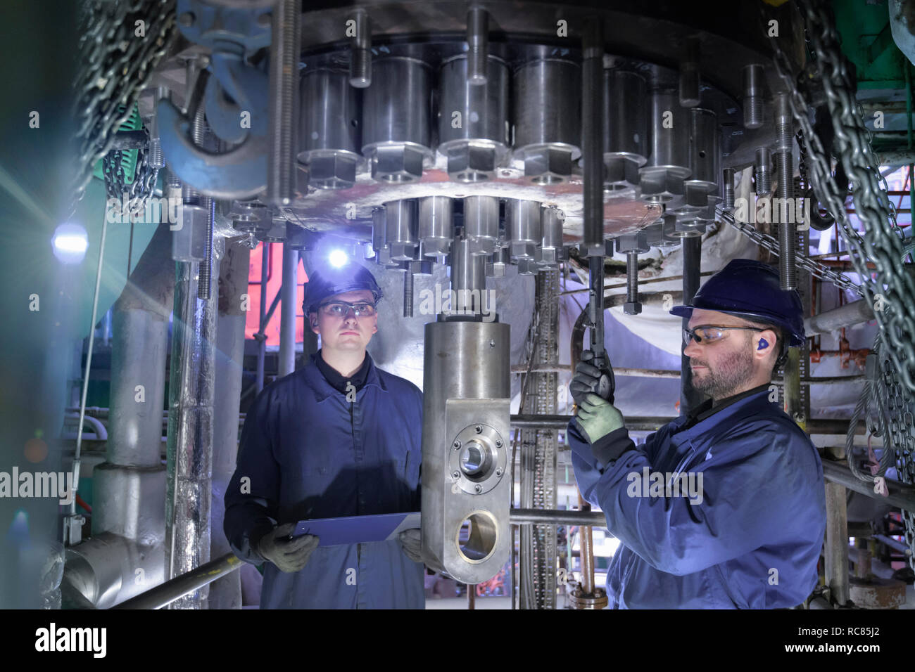 Engineers working in confined space under turbine during outage in nuclear power station - Stock Image