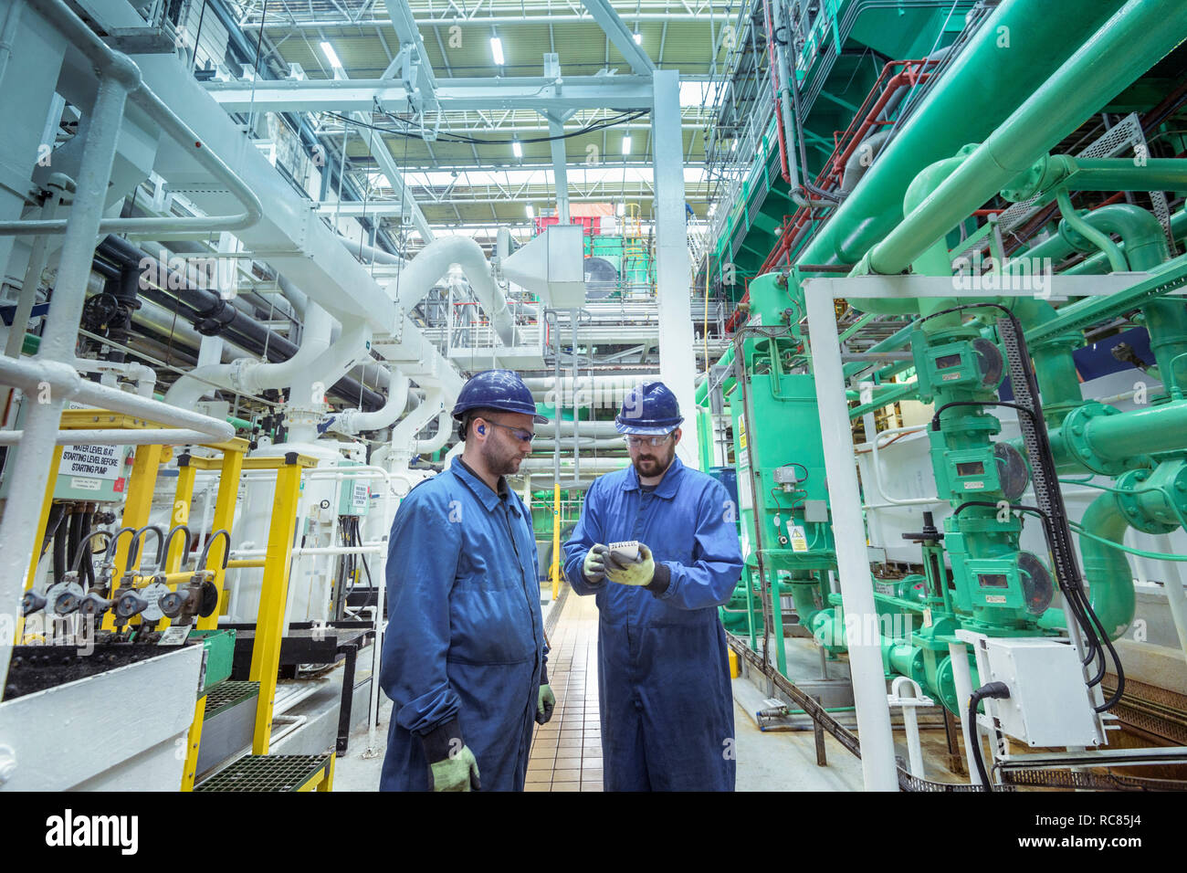 Engineers in turbine hall in nuclear power station - Stock Image