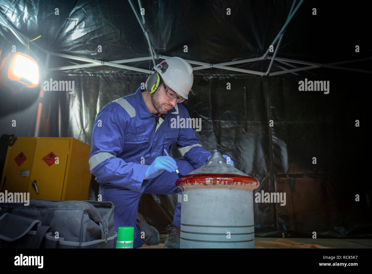 Engineer crack testing large part in turbine hall of nuclear power station - Stock Image