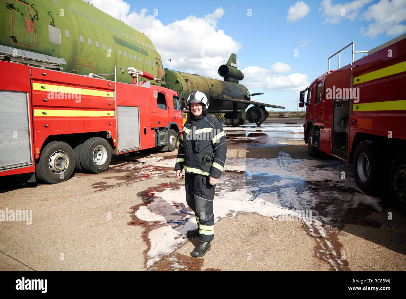 Fire training, fireman by fire engines at training facility, portrait - Stock Image