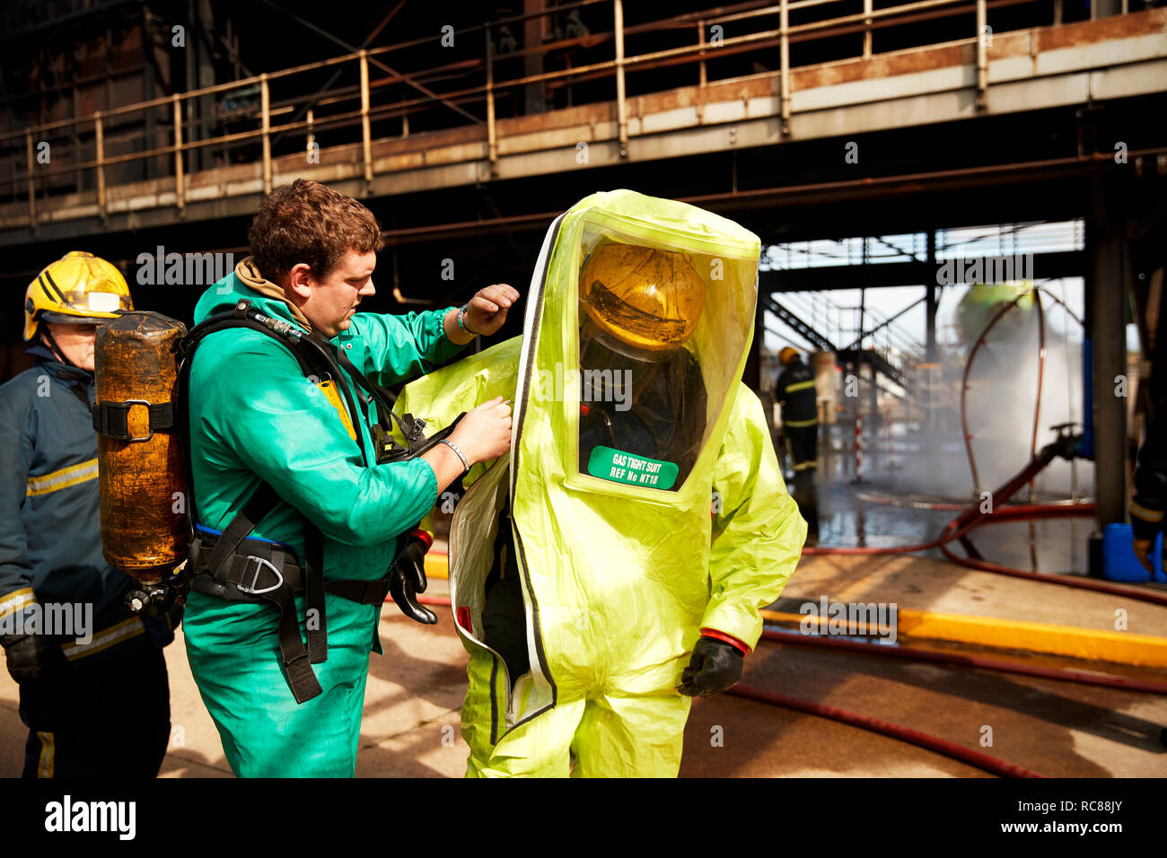 Firemen putting on fire proximity suit in training centre, Darlington, UK - Stock Image