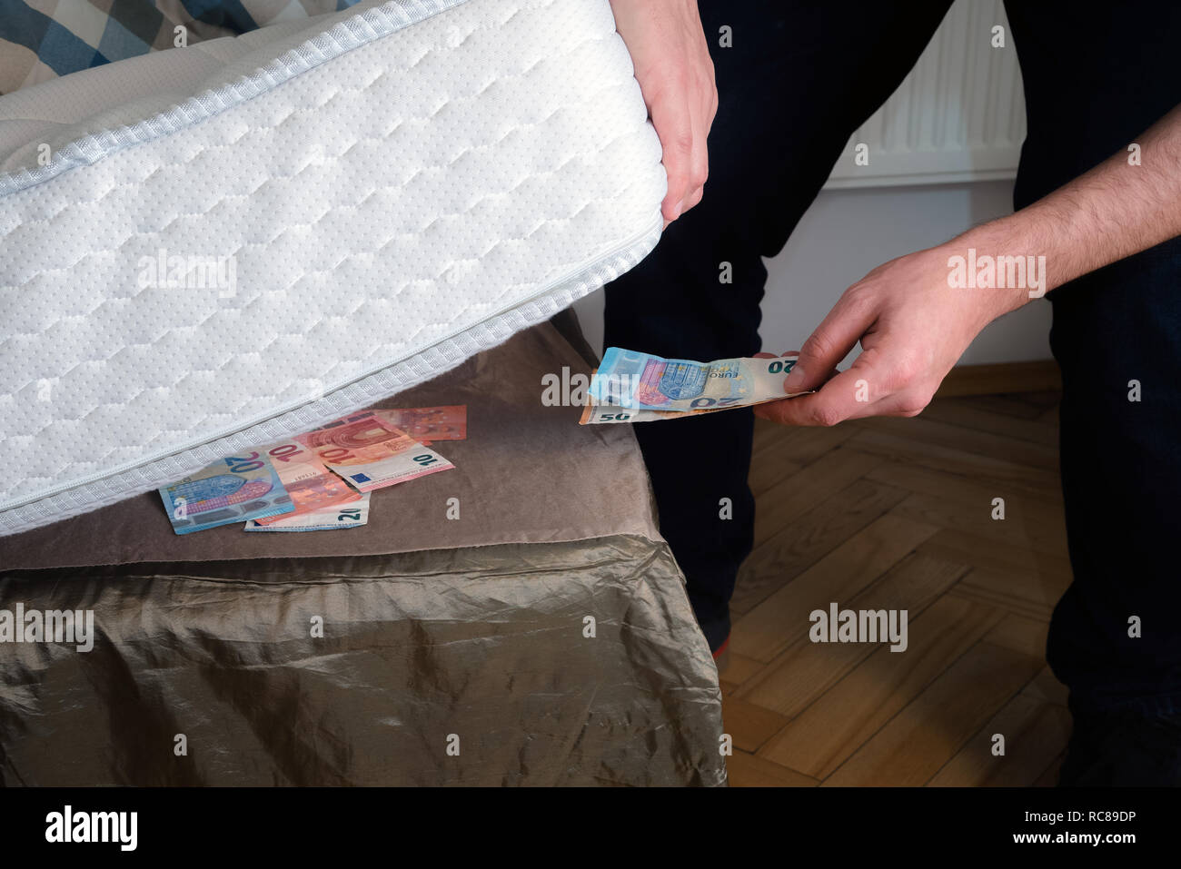 Man putting money under his mattress to save it. Showing no trust in financial institutions and banks, black market Stock Photo