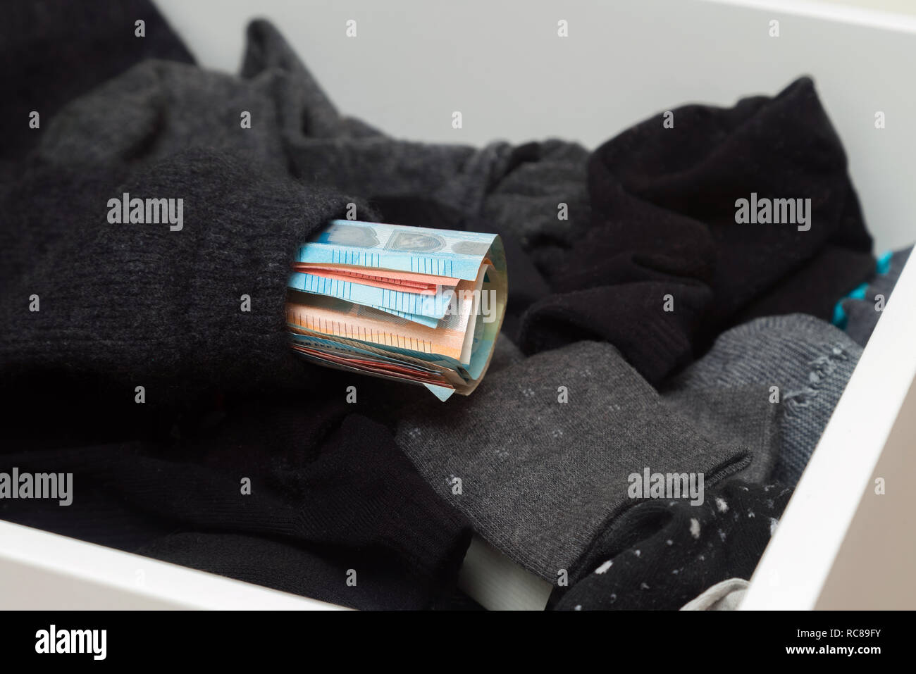 Man putting, hiding money in his socks to save it. Showing no trust in financial institutions and banks, black market - Stock Image