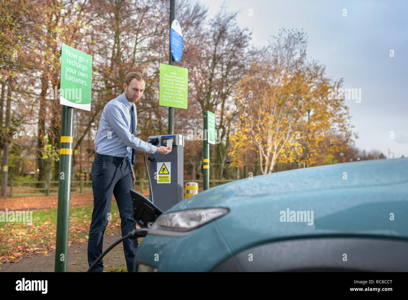 Man charging electric car at charge point, Manchester, UK - Stock Image