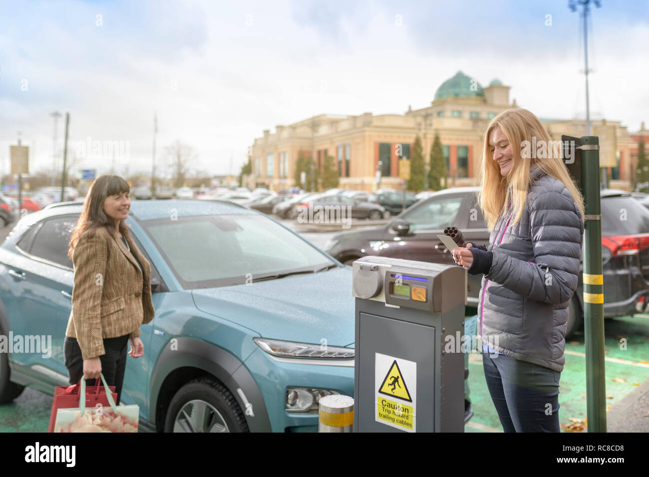 Female shoppers charging electric car at charge point, Manchester, UK - Stock Image