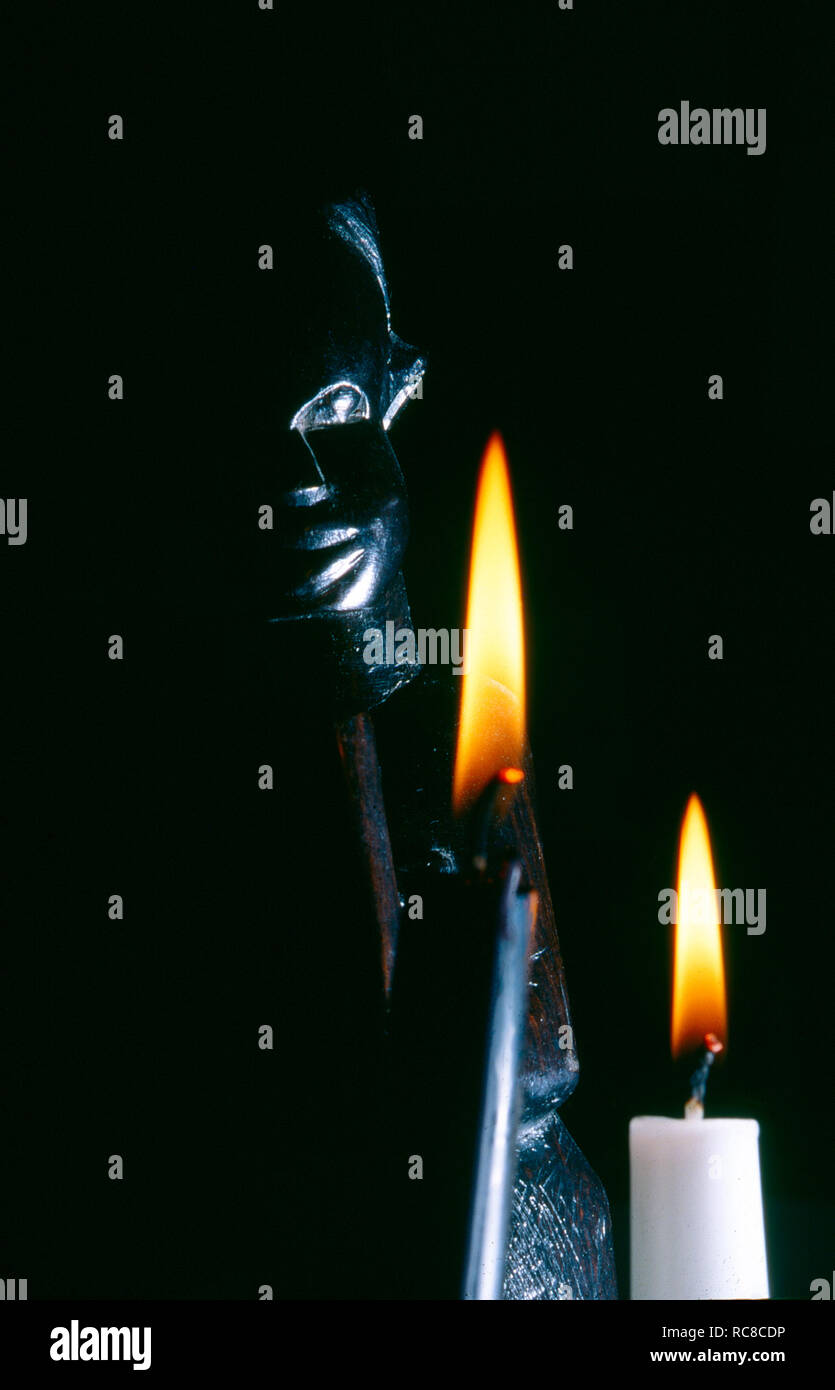 dark close-up image of an african statue with two burning candels - Stock Image