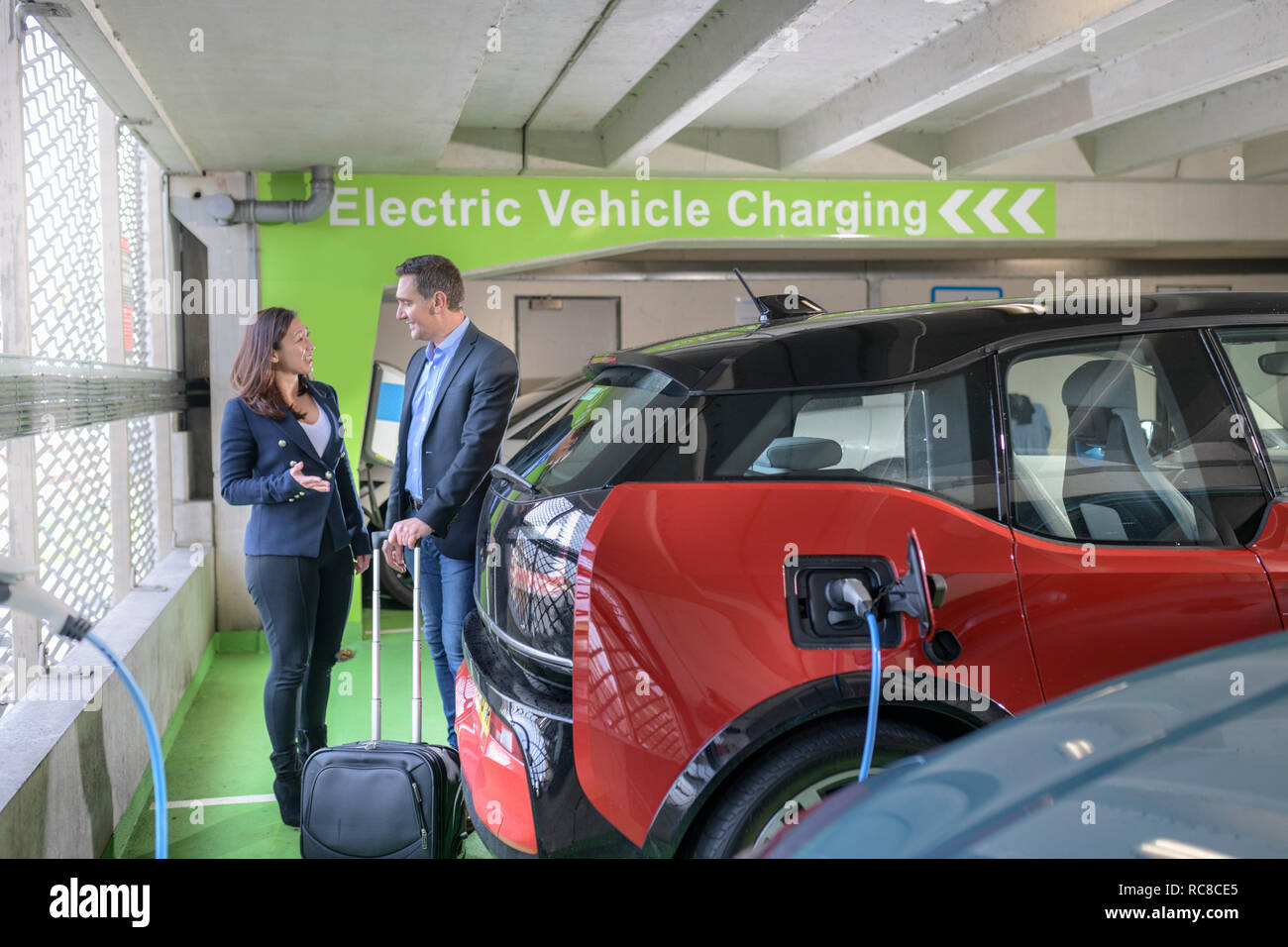 Man and woman charging electric car at charge bay, Manchester, UK Stock Photo