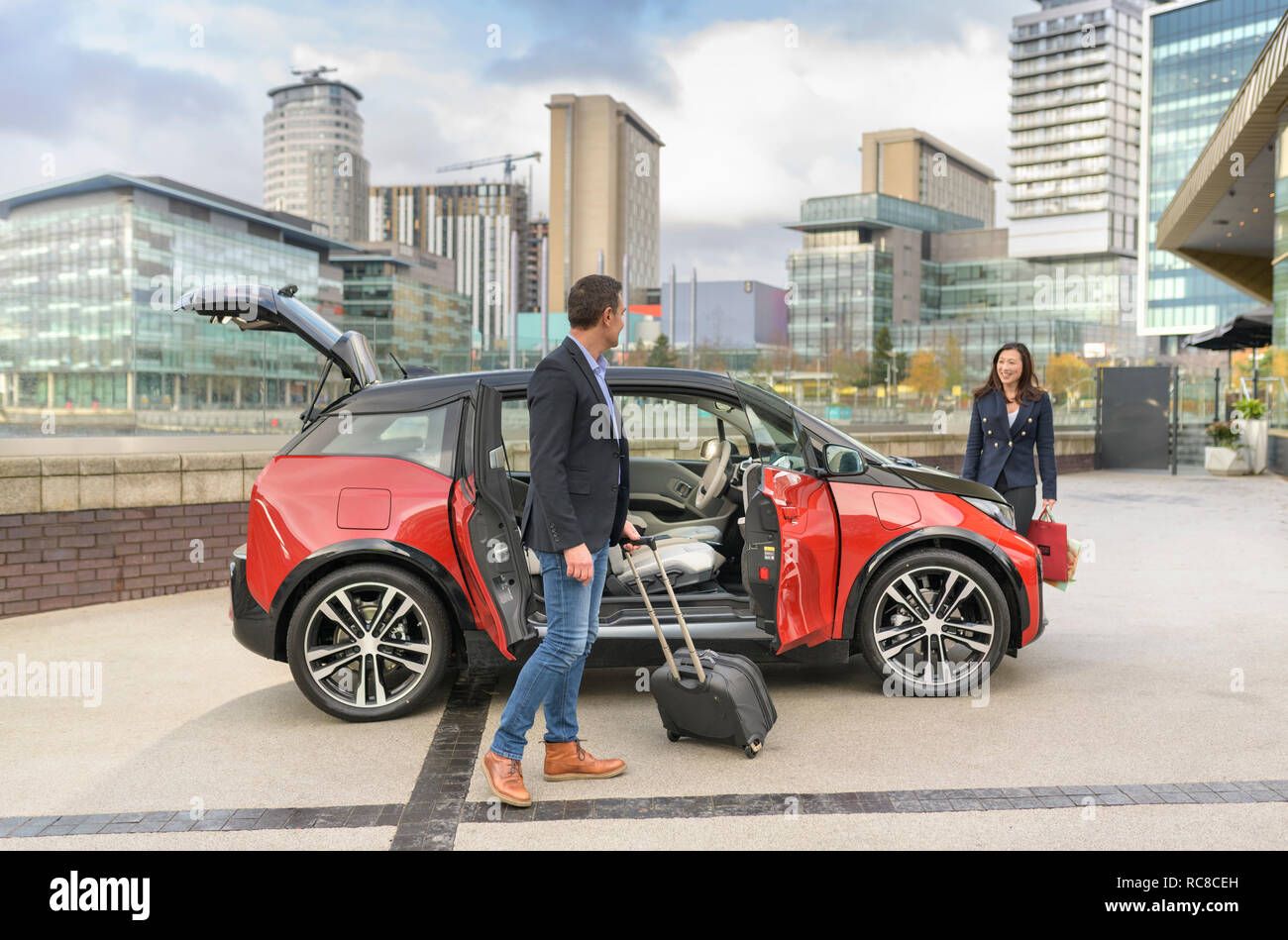 Man and woman with parked electric car, Manchester, UK - Stock Image