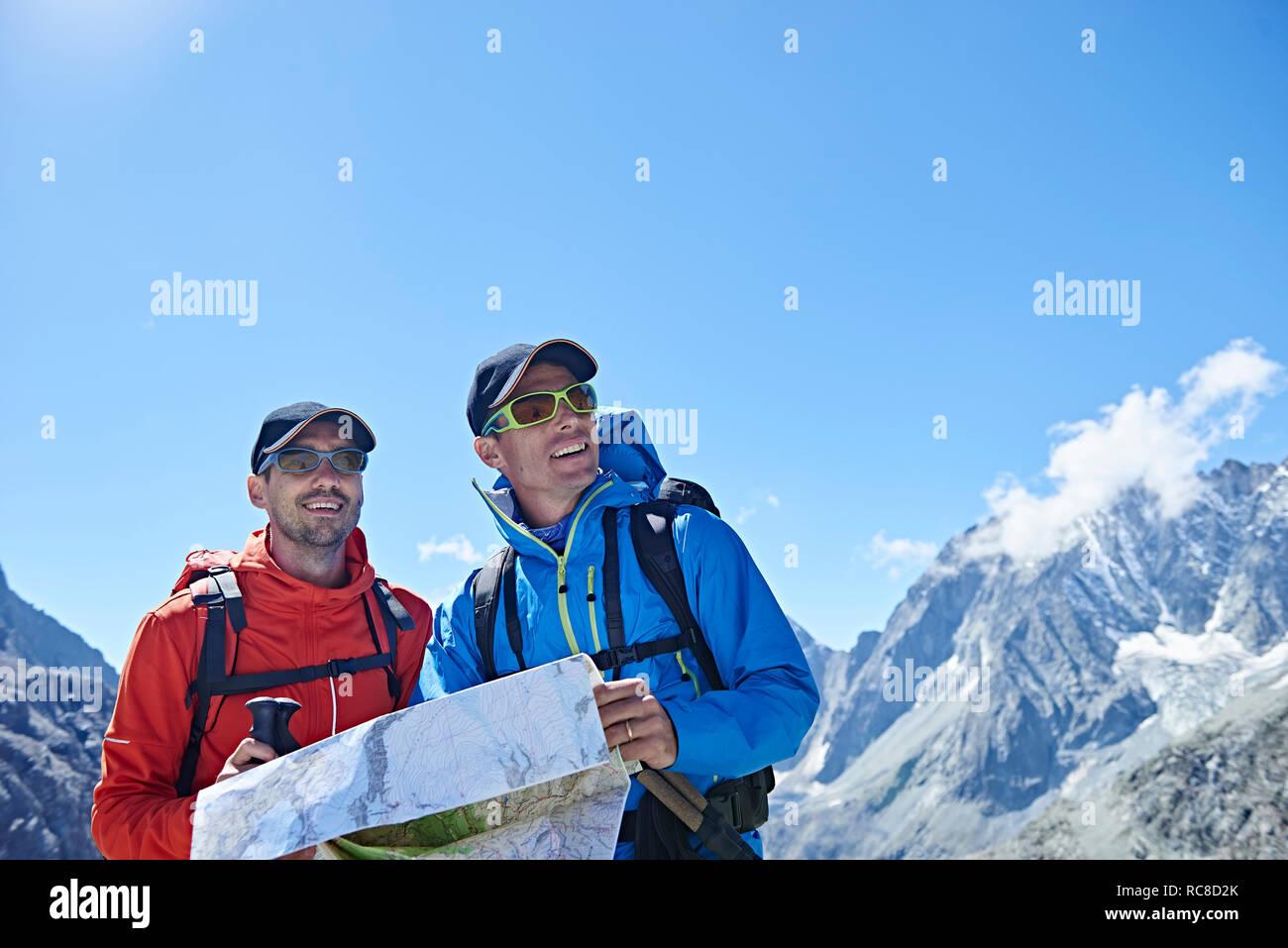 Hiker friends reading map, Mont Cervin, Matterhorn, Valais, Switzerland Stock Photo