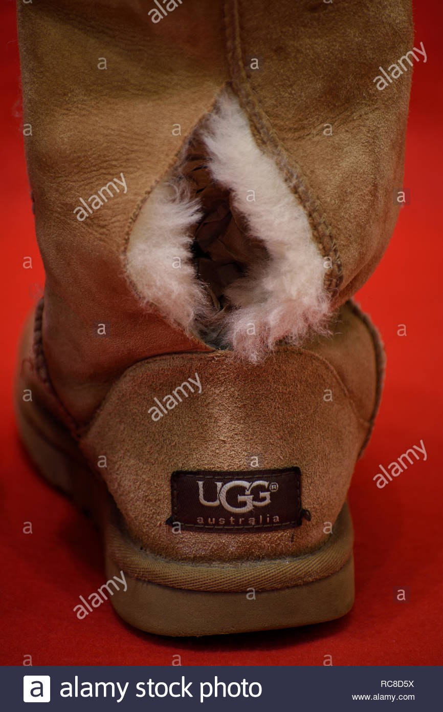 Torn UGG Boots. UGG Boots with hole. Ripped Ugg Boot. UGG Boot is torn along seam. Shearling. Sheepskin. UGG Australia. Worn Out UGG Boots. UGGS. Torn Stock Photo