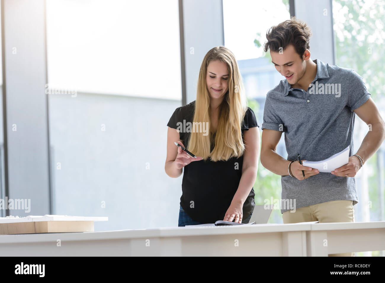 Colleagues brainstorming by glass wall Stock Photo