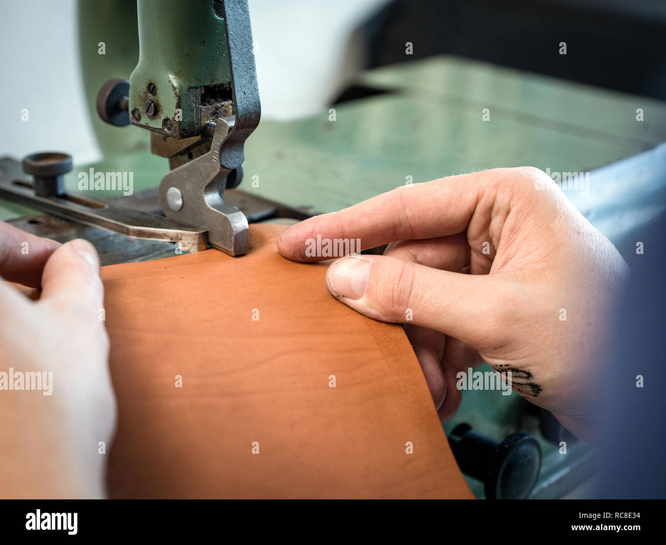Leatherworker using machining leather handbag edge in workshop, close up of hands - Stock Image