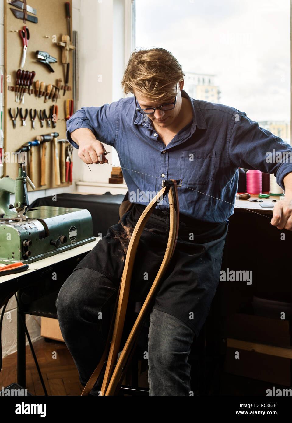 Leatherworker stitching leather handbag straps in workshop Stock Photo