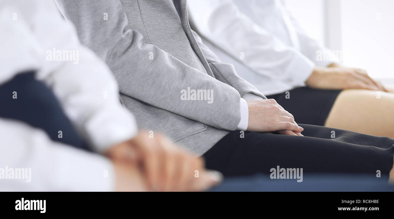Business people waiting for job interviews or taking part at conference in office, close-up. Women sitting on chairs like at queue or meeting - Stock Image
